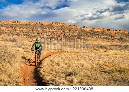 senior male cyclist riding a fat bike on a trail in Colorado foothills (Lory State Park near Fort Collins), a typical cold, but snowless winter afternoon