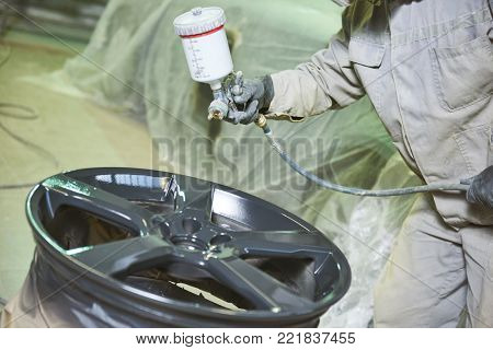 Automobile disc restoring. Painter painting light alloy wheel with spray