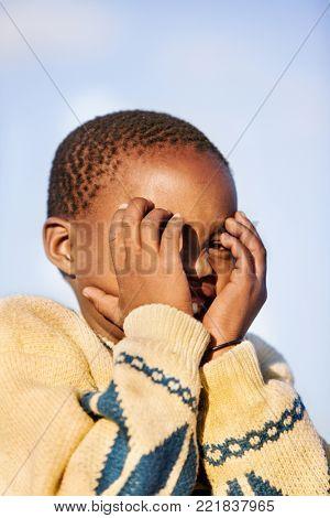 Motswana child smiling against sky background hiding face