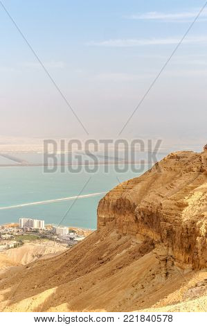 Beautiful nature view from desert on stone mountain and dead sea. Outdoor scenic picturesque landscape of mountains, sand and rocks. Travel in middle east