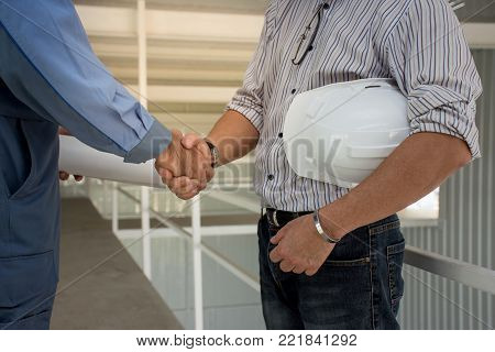 Two professional engineering team with White helmet  shaking hands to each other at construction site.