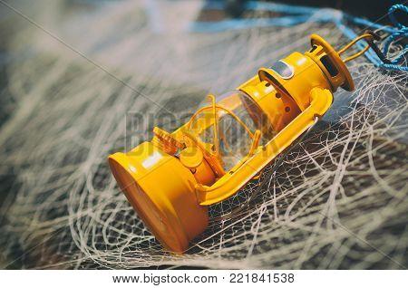Old yellow kerosene lamp or lantern hanging with fishing net