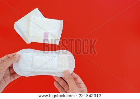 Hand holding feminine sanitary napkin, an absorbent item worn by a woman while menstruating, on red background with copy space  for hygiene and health concept
