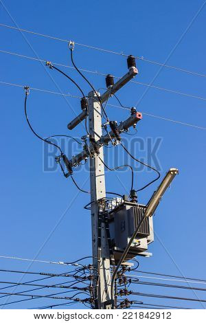 Electric pole connect to the high voltage electric wires on against bright blue sky