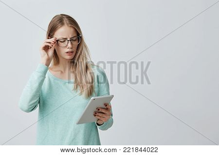 Attractive blonde female manager in stylsh eyewear works, look nervously at screen of tablet finds out unpleasant news. Annoyed young Caucasian woman dressed in light blue sweater uses modern technologies.