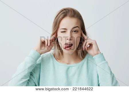 Studio portrait of bored and annoyed young blonde female frowning and plugging ears with fingers can't stand noise or ignoring stressful unpleasant situation, sticking out tongue. Negative human emotions