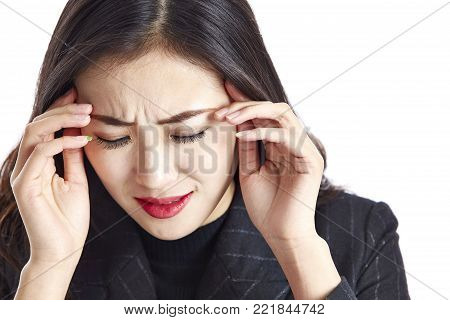studio shot of a young asian business woman having a headache, painful and miserable, hand on temple, isolated on white background.