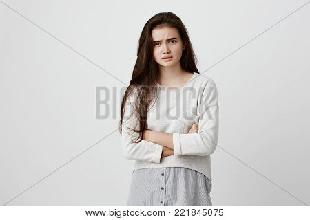 Indoor shot of dissatisfied offended beautiful young brunette dressed casually keeping arms folded, looking at camera with strict and skeptical expression, doesn't believe in excuses of her unfaithful boyfriend