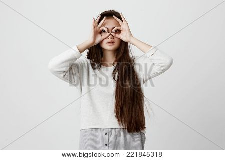 Playful excited teenage female with dark long straight hair showing Ok gestures with both hands, pretending to wear spectacles, astonished to see something amazing. Emotions, feelings, body language and gestures