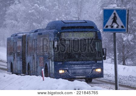 UMEA, SWEDEN ON DECEMBER 11. View of a bus pass a zebra crossing along a snowy road on December 11, 2017 in Umea, Sweden. Trees in the background. Editorial use.