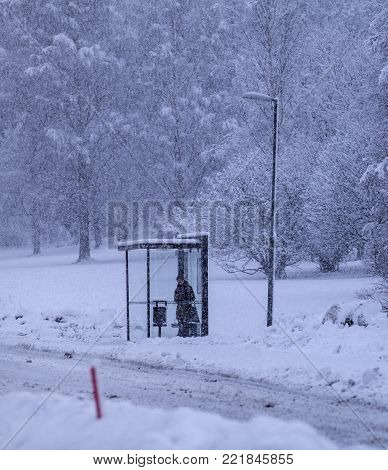 UMEA, SWEDEN ON DECEMBER 11. Passenger wait for the bus at a bus stop on December 11, 2017 in Umea, Sweden. Unidentified person, snowy conditions. Editorial use.