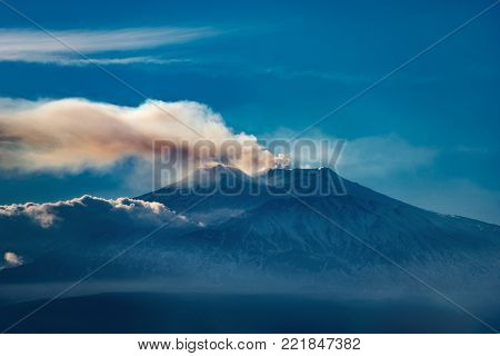 The mount Etna Volcano with smoke in Sicily island, Catania, Italy (Sicilia, Italia). Seen from the city of Taormina
