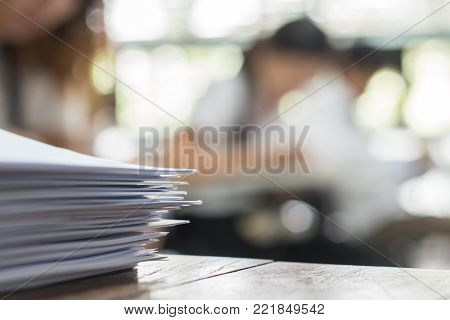 Exam answer sheet or application paper blurry view on table in examination room with blur education background of school university students taking exam test writing answer in seat row with stress