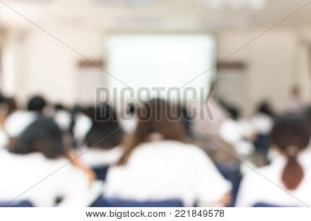 School classroom blurred background of college or university students back view sitting in class in seating rows studying learning course in lecture room with white projector screen in front