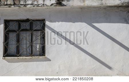 white wall of the house, a window on the wall, two parallel shadows create a rhythm in the photo, the sun's backlight creates an effect of the peace of the world, pacification, the photo gives a sense of antiquity
