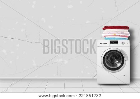 Major appliance - Washing machine and linen pile in home interier on a light wall background.