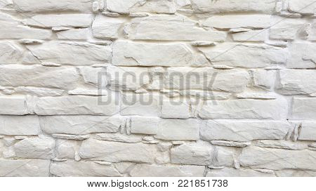 White painted stone wall texture as background. Cracked concrete vintage block stone wall background, old painted wall. Background wall painting