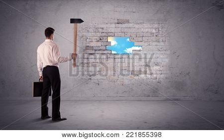 Business man hitting grungy brick wall with hammer