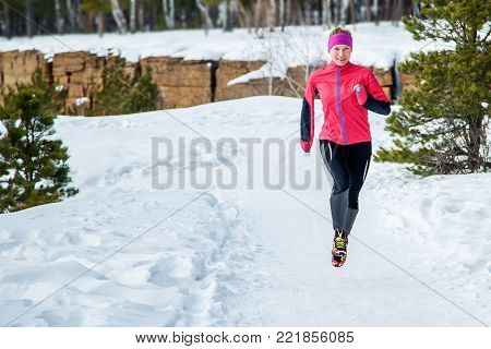 Running sport woman. Female runner jogging in cold winter forest wearing warm sporty running clothing. Fitness happy girl running in winter park. Fitness and healthy lifestyle concept