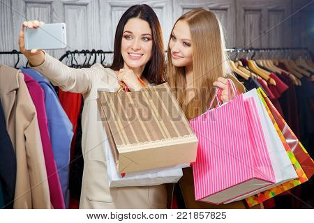 Fashion portrait of two young beautiful women friends in shopping mall with a lot of shopping bags. Making selfie. Smiling and happy after shopping.