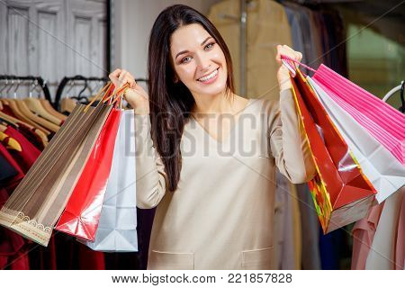 Portrait of a happy girl with purchases. Beautiful woman with shopping bags in a shopping center. Buyer. Sales. Shopping center