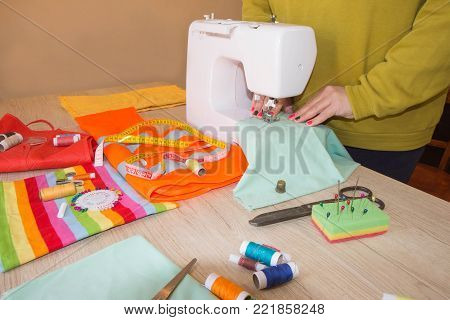 Tailoring of natural cotton. Woman tailors sewing fabric. Tailor Woman, fashion designer working at studio