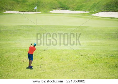 Golfer hitting golf shot with club on course while on summer vacation,Man playing golf on a golf course in the sun