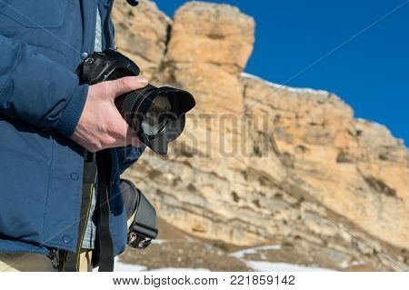 A close-up of the hand of the traveler's photographer keeps the camera in hand against the background of yellow rocks in the winter in the Caucasus. The concept of travel and photography in travel