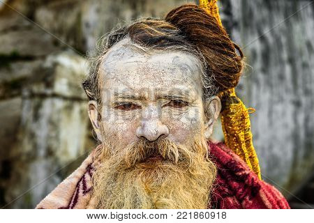 KATHMANDU, NEPAL - OCTOBER 21, 2015 : Portrait of wandering Shaiva sadhu with traditional face painting in ancient Pashupatinath Temple