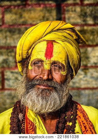KATHMANDU, NEPAL - OCTOBER 21, 2015 : Portrait of sadhu baba with yellow face painting in ancient Pashupatinath Temple