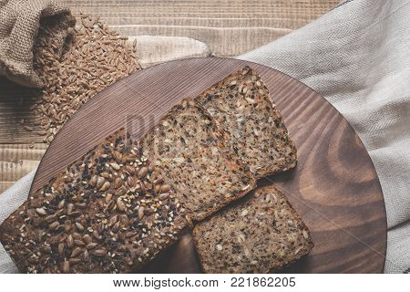 Fitness bread. Cut with slices and whole grain bread on a wooden board. A loaf of fresh rustic whole meal rye bread, sliced on a wooden board, rural food background. Top view.
