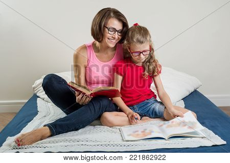 Mother and little daughter read books at home in bed.