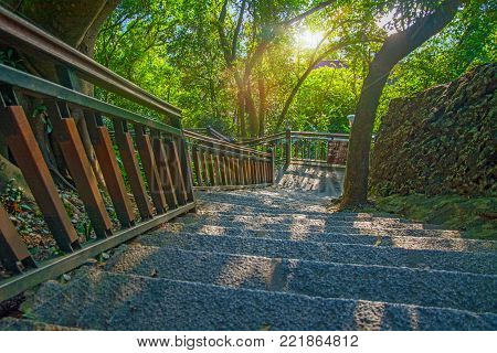 large stone staircase in a beautiful dense forest of rock staircase descends to the park, Asia China.
