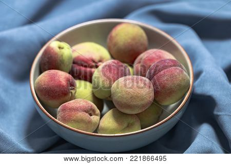 Vineyard peaches in gray bowl on blue background