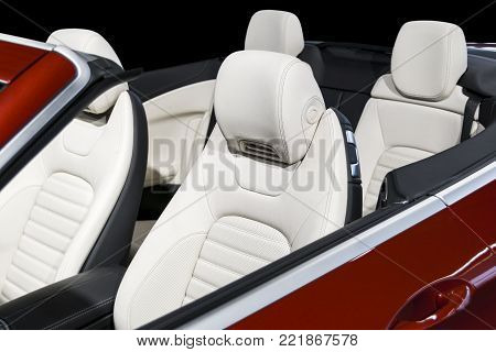Modern Luxury car inside. Interior of prestige modern car. Comfortable leather seats. White perforated leather cockpit with isolated Black background. Modern car interior details