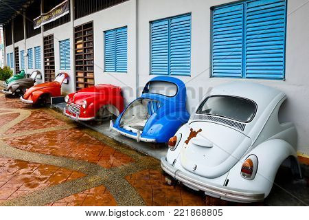 MALACCA MALAYSIA SEPTEMBER 20 2017: Old cars decorate a market building in Malaysia's colorful and historic World Heritage City, Melaka