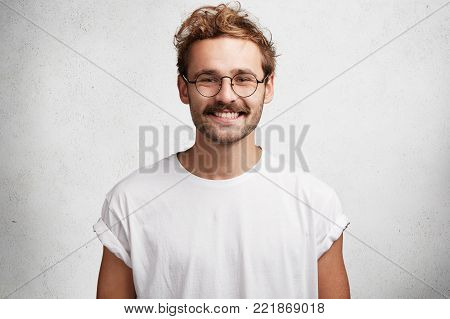Photo Of Serious Confident Fashionable Male With Trendy Hairdo, Wears Round Spectacles And White T S