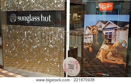 Sydney, Australia - November 03, 2017: Sunglass Hut retail store exterior with huge Ray-Ban advertisement poster on display.