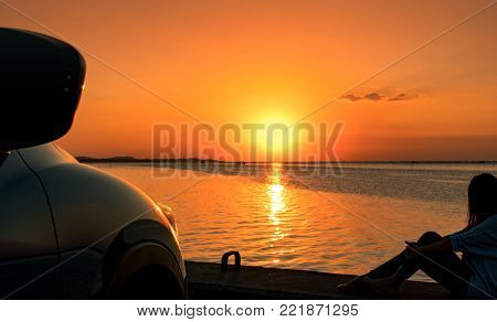 Lonely young woman wear a cap relaxing on the beach alone in front of the car with orange and blue sky at sunset. Summer vacation and travel concept.