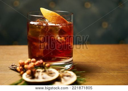 Beverage cocktail with cognac or whiskey cola ice cubes and lime on wooden table on dark background with copy space for text. alcoholic drink