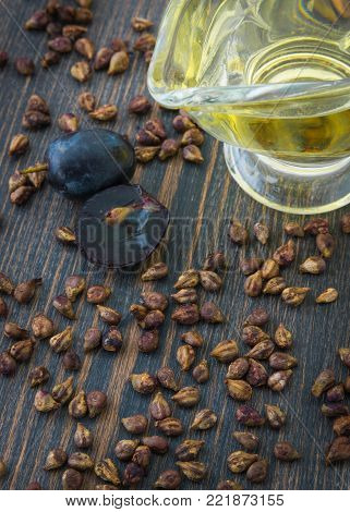 Grape seeds and natural grape-seed oil on dark wooden background