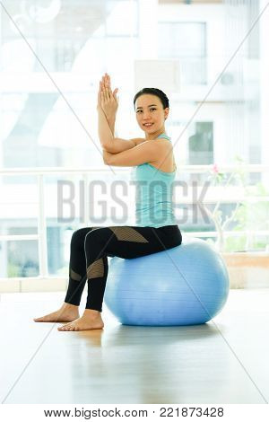 Young asian women practicing yoga ball, fitness stretching flexibility pose, working out, healthy lifestyle, wellness, well being
