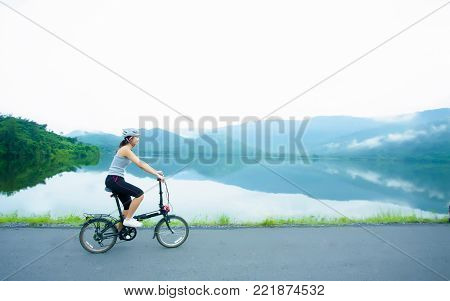 Thai sport girl is cycling in the morning on the lakeside