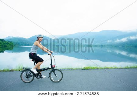 Young women riding the bicycle on the lakeside in the morning