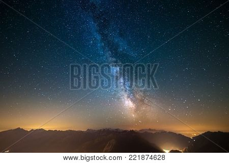Milky Way and starry sky captured at high altitude in summertime on the Alps with glowing Aosta Valley below, travel destination in Italy.