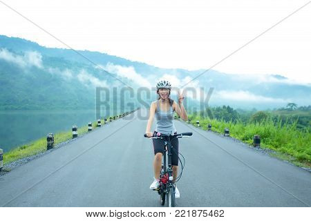 Cheerful young sport girl cycling on the lakeside in the morning