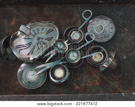 Pair of long curved scissors and watches of different sizes of deformed dials make up the composition against a rusty iron background.