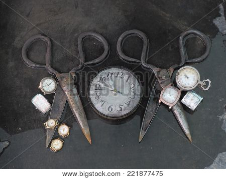 Two ancient scissors hand forging lie open on a black background, between them a clock alarm clock, on the blades are scattered small wristwatch, modern interior design of the wall.