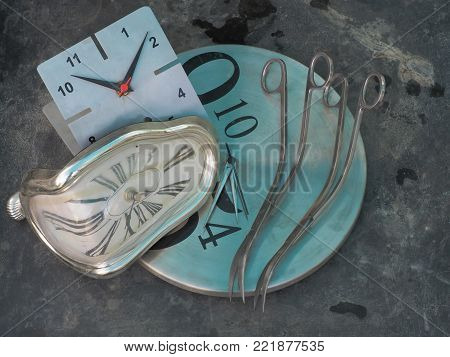 Pair of curved curves long scissors for shearing plants on the edge of a round dial wall clock, to the left still parv wall clock with a curved surface, gray background.