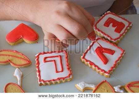 women in the kitchen prepare for the Valentine's Day. woman prepares Valentine's Day cookie. adorns heart shapes with his hands. ornamentation and shaping